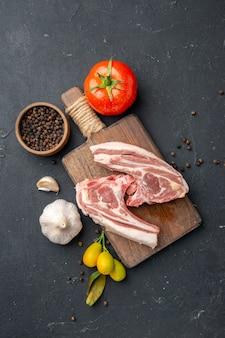 Bovenaanzicht vers vlees ribben rauw vlees met kruiden op donkere barbecue dierenschotel peper keuken eten koe salade maaltijd eten