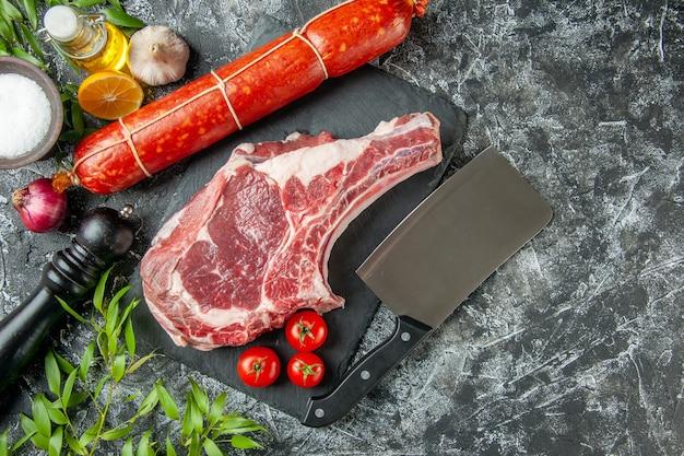 Bovenaanzicht vers vleesplakje met toamtoes op lichtgrijze achtergrond dierlijke koe kippenvlees slager voedsel keuken kleur