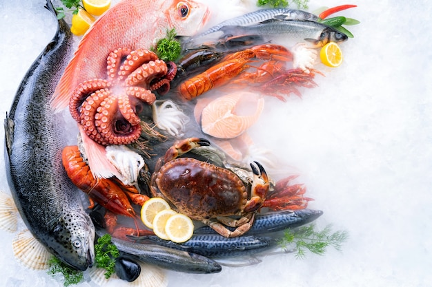 Bovenaanzicht verscheidenheid aan verse luxe zeevruchten op ijs achtergrond met ijzige rook in vismarkt