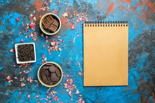 Bovenaanzicht verschillende chocolaatjes in kleine kommen kladblok op blauw rood oppervlak