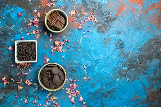 Bovenaanzicht verschillende chocolaatjes op blauw rood oppervlak vrije ruimte