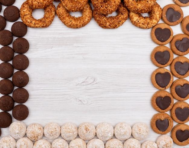 Bovenaanzicht, verschillende cookies met kopie ruimte op witte ondergrond