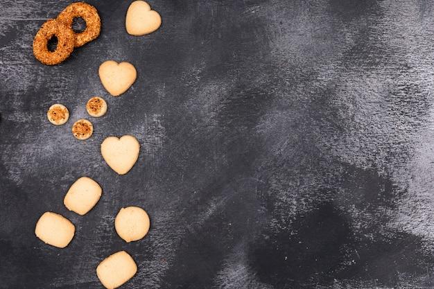Bovenaanzicht, verschillende cookies op donkere ondergrond