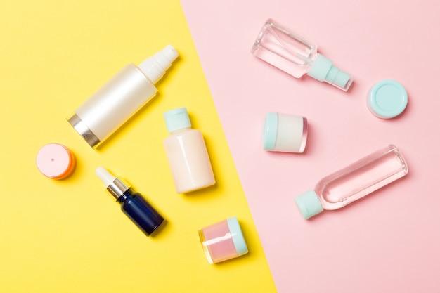 Bovenaanzicht verschillende cosmetische flessen en container voor cosmetica op roze en geel. plat lag samenstelling copyspace