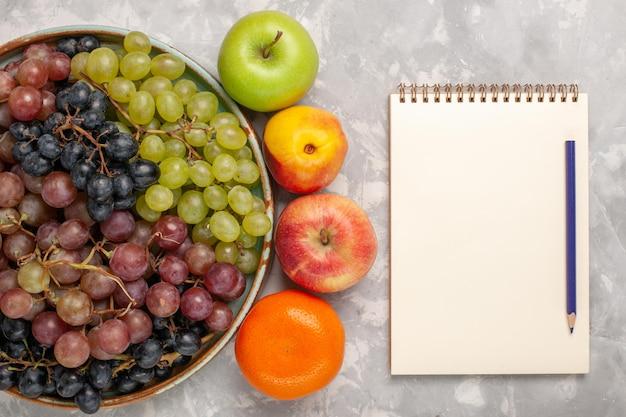 Bovenaanzicht verschillende druiven met ander fruit op het lichtwitte bureau