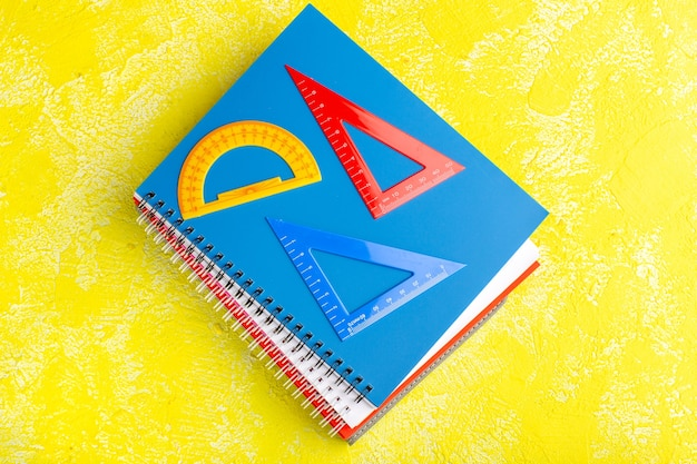 Bovenaanzicht verschillende figuren met voorbeeldenboeken op het gele vlak