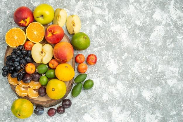 Bovenaanzicht verschillende fruitsamenstelling gesneden en geheel vers fruit op witte achtergrond boom vitamine rijp fruit zachte kleur
