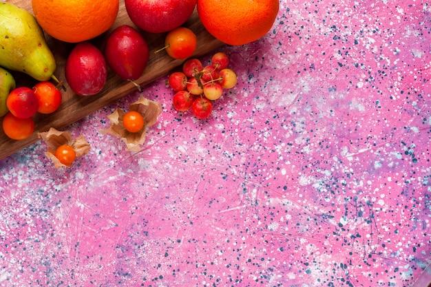 Bovenaanzicht verschillende fruitsamenstelling vers en zacht fruit op roze bureau.
