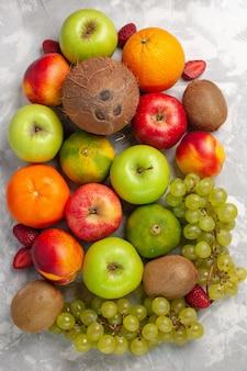 Bovenaanzicht verschillende fruitsamenstelling vers fruit op wit bureau