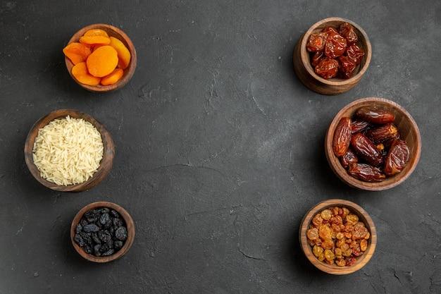 Bovenaanzicht verschillende gedroogde rozijnen in potten op donkere ondergrond droog fruit zure khurma rozijn