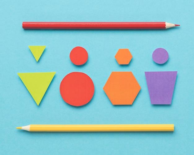 Bovenaanzicht verschillende gekleurde geometrische vormen op blauwe achtergrond