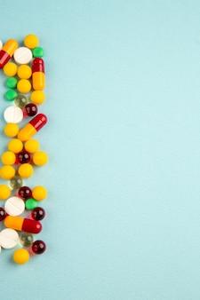Bovenaanzicht verschillende gekleurde pillen op blauwe achtergrond