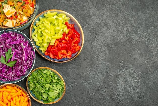 Bovenaanzicht verschillende gesneden groenten met kipsalade op donkere tafel gezondheidssalade dieet