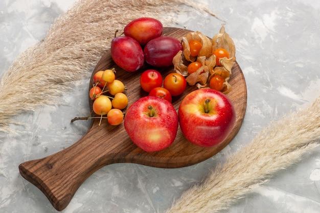Bovenaanzicht verschillende gevormde pruimen zuur en vers fruit met rode appels op lichtwit bureau.