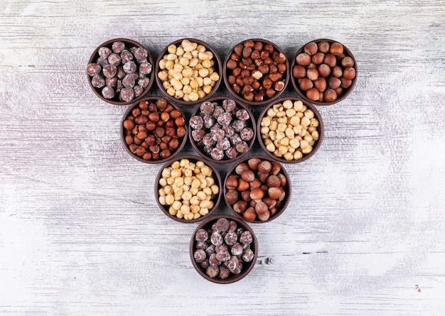 Bovenaanzicht verschillende hazelnoten in bruine kommen met geschilde, schoongemaakte hazelnoten op witte houten tafel. horizontaal