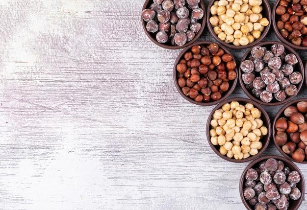 Bovenaanzicht verschillende hazelnoten in bruine kommen met geschilde, schoongemaakte hazelnoten op witte houten tafel.