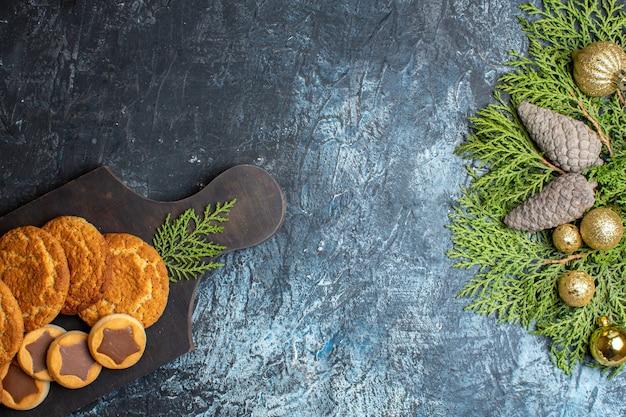 Bovenaanzicht verschillende heerlijke koekjes en dennentakken met dennenappel
