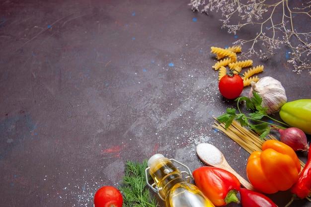 Bovenaanzicht verschillende ingrediënten rauwe pasta en verse groenten op de donkere achtergrond product voedsel gezondheid salade dieet Gratis Foto
