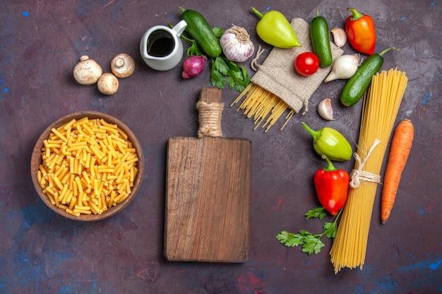 Bovenaanzicht verschillende ingrediënten rauwe pasta en verse groenten op een donker bureau product verse maaltijdsalade gezondheidsdieet