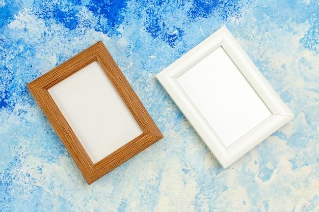 Bovenaanzicht verschillende kleuren lege fotolijsten op blauw witte grunge