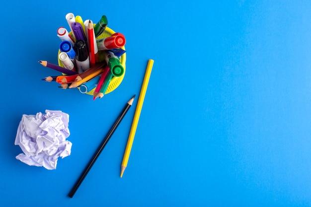 Bovenaanzicht verschillende kleurrijke potloden met viltstiften op blauw bureau