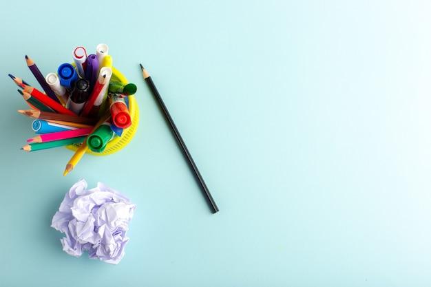 Bovenaanzicht verschillende kleurrijke potloden met viltstiften op blauwe ondergrond