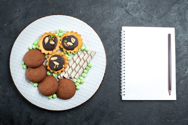 Bovenaanzicht verschillende koekjes chocolade gebaseerd met snoepjes op grijze achtergrond candy bonbon suiker zoete cake cookie