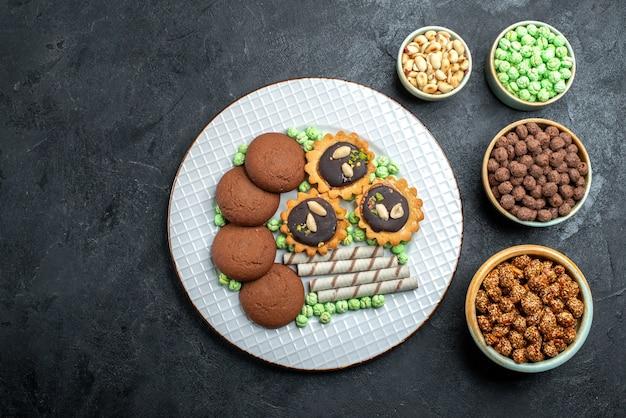 Bovenaanzicht verschillende koekjes chocolade gebaseerd met verschillende suikersuikergoed op grijze ondergrond candy bonbon suiker zoete cake cookie