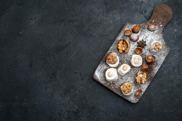 Bovenaanzicht verschillende koekjes met cakes en walnoten op het donkergrijze oppervlak