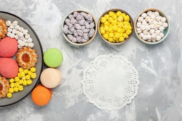 Bovenaanzicht verschillende koekjes met franse macarons en snoepjes op witte achtergrond snoep suiker zoete bak cake thee taart cookie