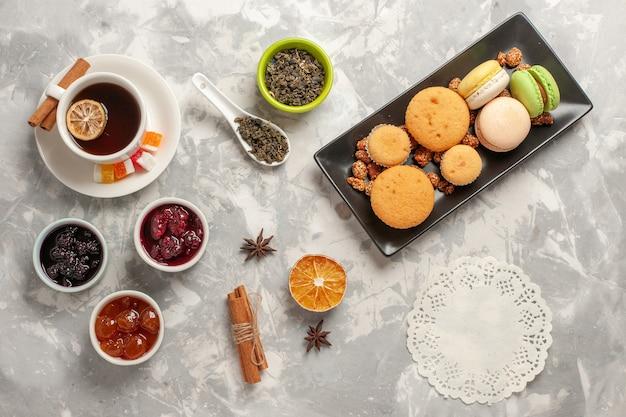 Bovenaanzicht verschillende koekjes met jam en kopje thee op het witte oppervlak biscuit sugar pie cake zoete koekjes