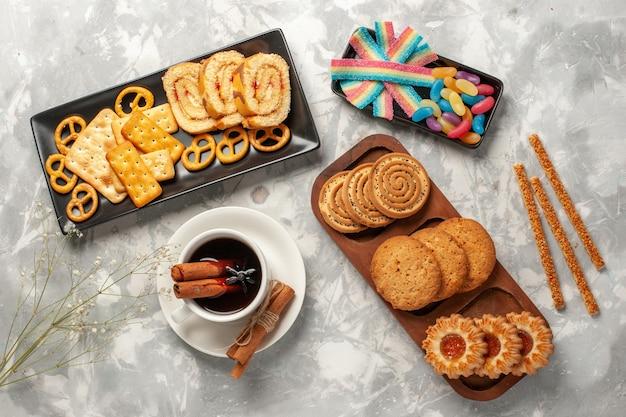 Bovenaanzicht verschillende koekjes met snoepjes en kopje thee op witte ondergrond koekjes biscuit suiker bakken cake zoete taart