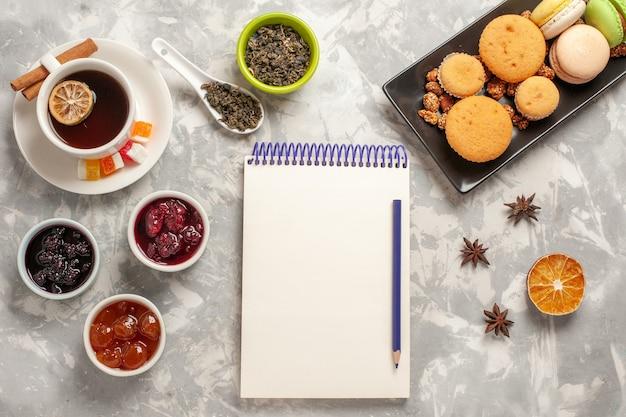 Bovenaanzicht verschillende koekjes met verschillende jam en kopje thee op witte achtergrond biscuit sugar pie cake zoete koekjes