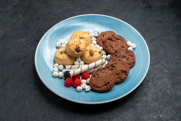 Bovenaanzicht verschillende koekjes zoete en heerlijke koekjes binnen op grijs bureau