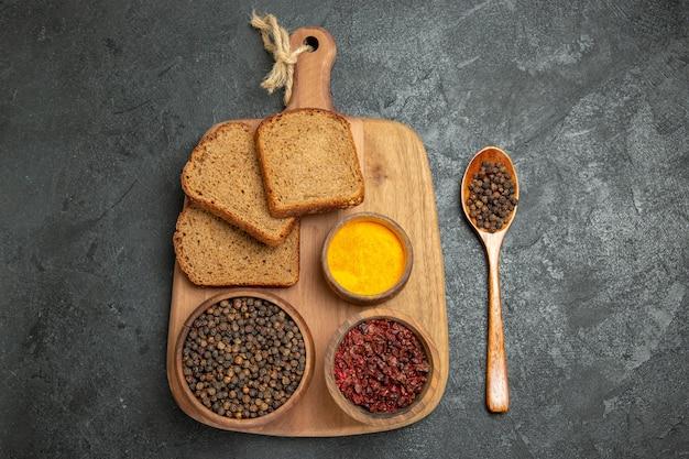 Bovenaanzicht verschillende kruiden met broodbroodjes op het grijze bureau brood pittig heet