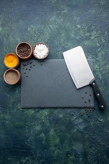 Bovenaanzicht verschillende kruiden met een groot mes op het donkerblauwe oppervlak, voedsel, kruiden, zout, peper, fotokleur