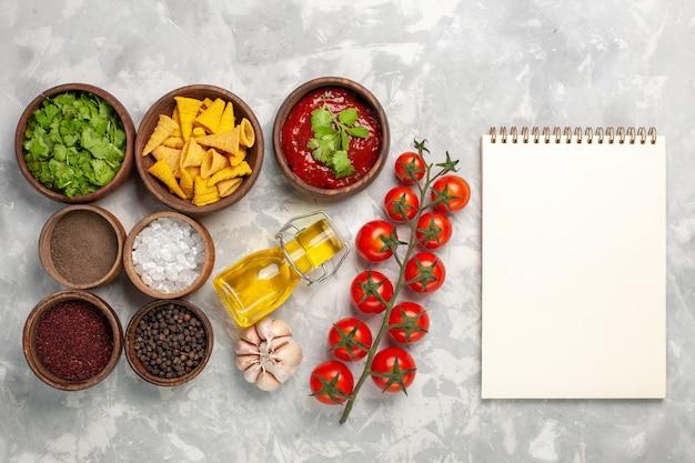 Bovenaanzicht verschillende kruiden met greens tomaten en olie op wit bureau
