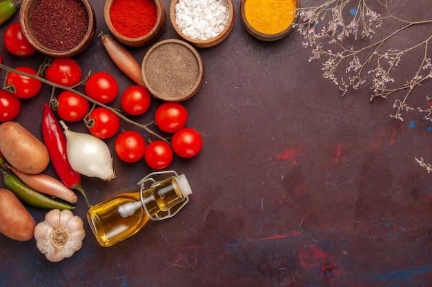 Bovenaanzicht verschillende kruiden met groenten op donker bureau