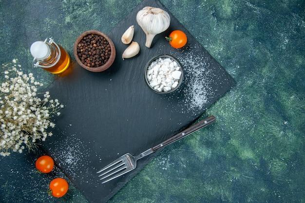 Bovenaanzicht verschillende kruiden met knoflook en olie op donkere achtergrond