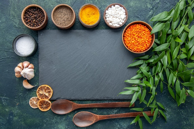 Bovenaanzicht verschillende kruiden met knoflook en oranje linzen op donkerblauwe achtergrond foto voedsel pittige hete peper kleur scherpe zaad soep