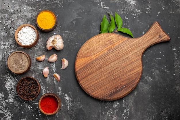 Bovenaanzicht verschillende kruiden met knoflook op donkere tafel kruiden kleur peper