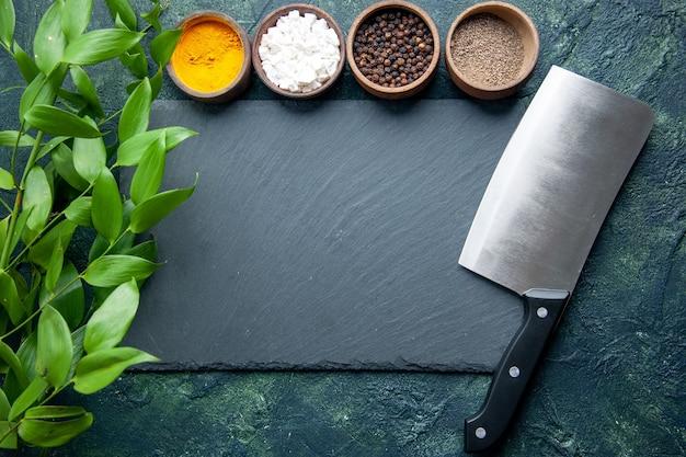 Bovenaanzicht verschillende kruiden met mes op donkerblauwe achtergrond foto voedsel kruiden zout peper