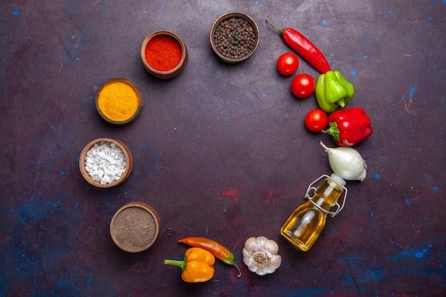 Bovenaanzicht verschillende kruiden met olie en groenten op donkere achtergrond maaltijd eten plantaardige pittig