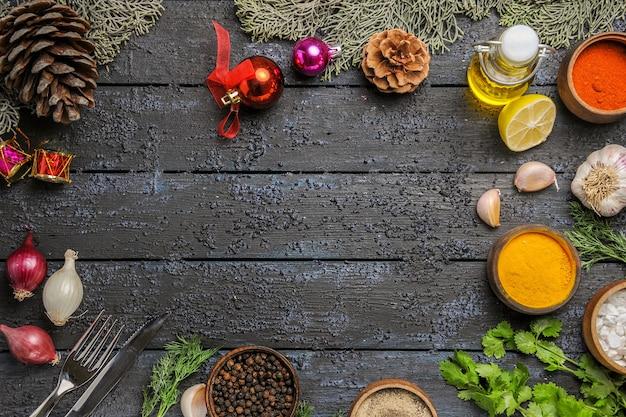 Bovenaanzicht verschillende kruiden met olie en knoflook op een donker bureau