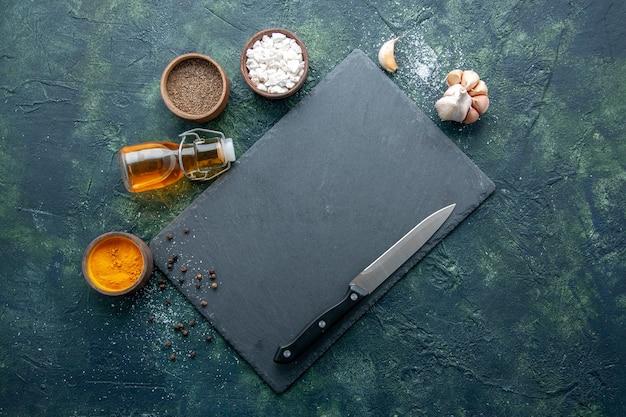 Bovenaanzicht verschillende kruiden met olie en mes op donkerblauwe achtergrond voedsel kruid peper schotel diner vlees kleur zout bakken