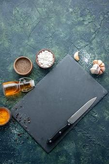 Bovenaanzicht verschillende kruiden met olie en mes op donkerblauwe tafel eten kruiden peper diner vlees kleur zout bakken