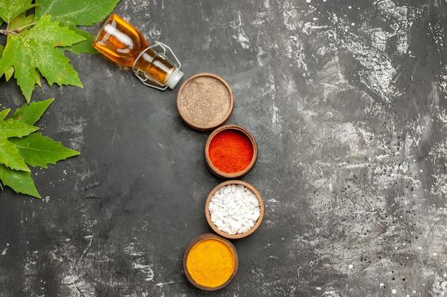 Bovenaanzicht verschillende kruiden met olie op een donkere ondergrond