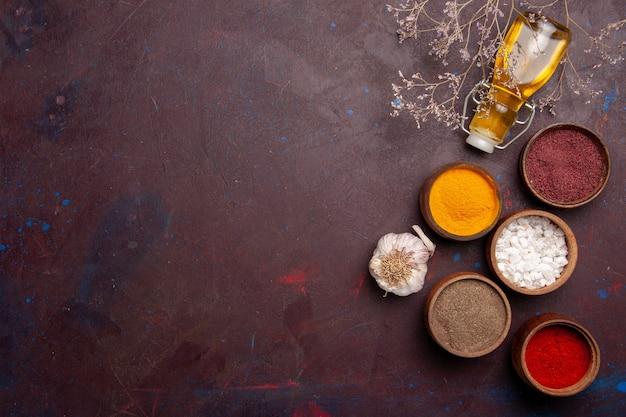 Bovenaanzicht verschillende kruiden met olijfolie op donkere ruimte
