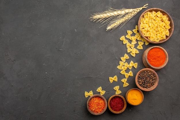 Bovenaanzicht verschillende kruiden met rauwe pasta op donkere achtergrond