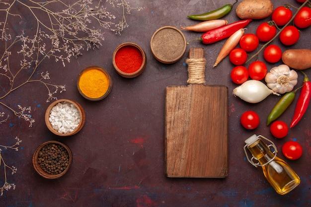 Bovenaanzicht verschillende kruiden met verse groenten op donkere ruimte